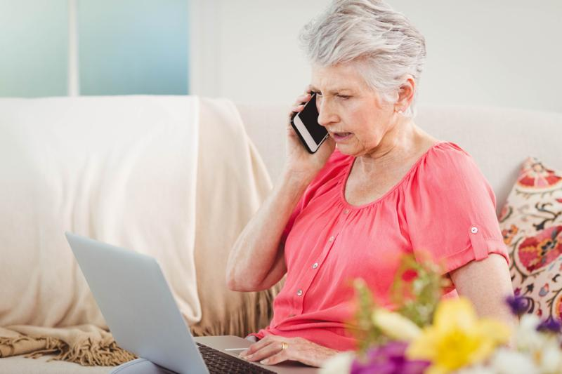 Senior woman talking on phone and using laptop in living room