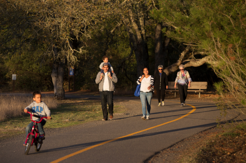 People walking on a regional parks pathway. Child on a bike.