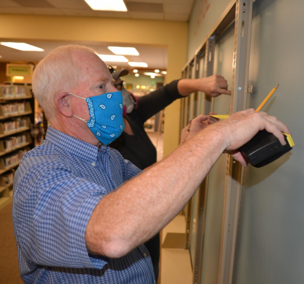 Library staff install new shelving for holds at Central Library