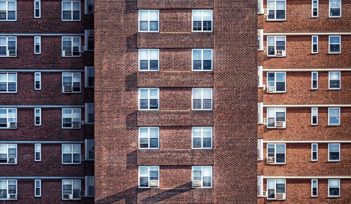 Windows of a large, brown brick apartment complex.