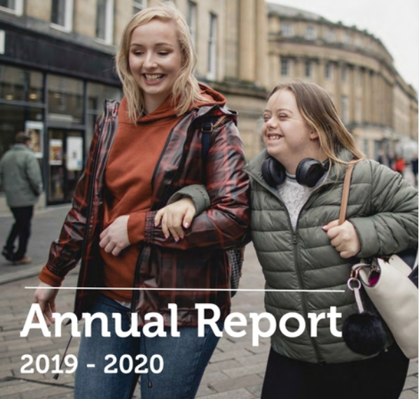 """Image of 2 friends walking downtown - the girl on the right has a disability. Text on image reads """"Annual Report 2019-2020"""""""