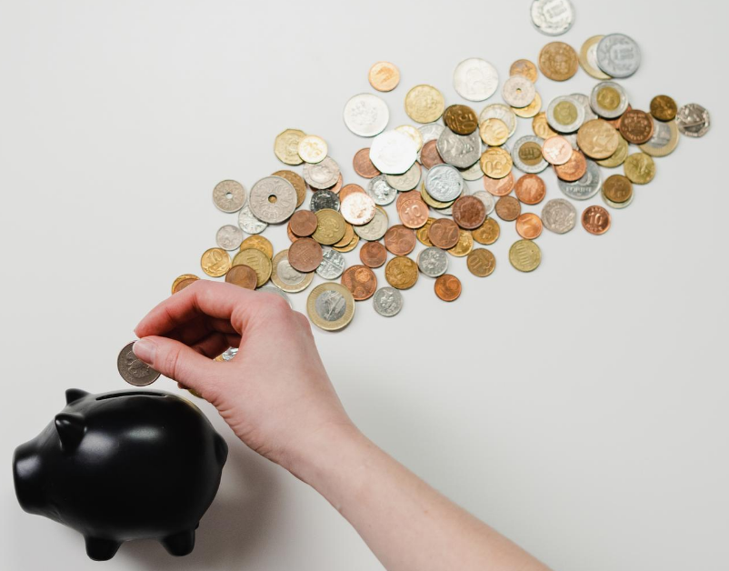 A pig-shaped piggy bank with coins spilled out across the screen and a hand putting a coin into the bank.