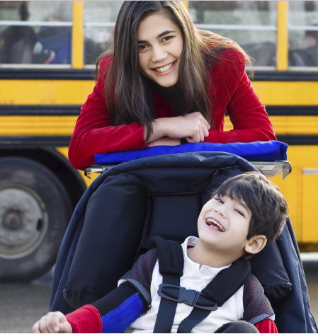 A child in a stroller with a disability smiling at the camera. A family member stands above, pushing the stroller and smiling. A yellow school bus is in the background.