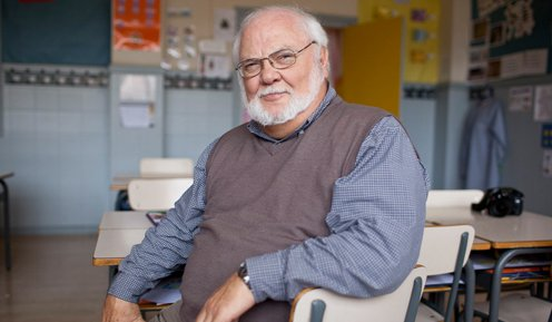 Image of Gordon Porter smiling at the camera while sitting in an elementary school classroom.