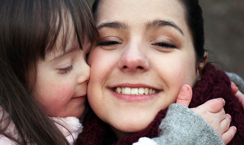 Mom with her daughter who has Down syndrome smiling at the camera.
