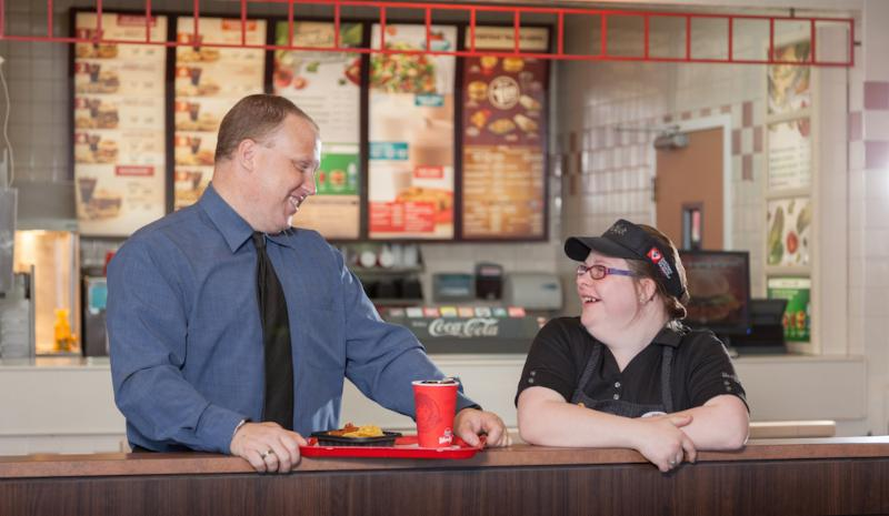 Wendy_s employee with Down Syndrome smiles along side her supervisor.