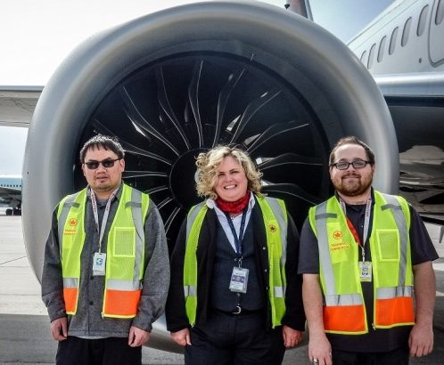2 men with disabilities and a woman smiling in front of an Air Canada jet engine.