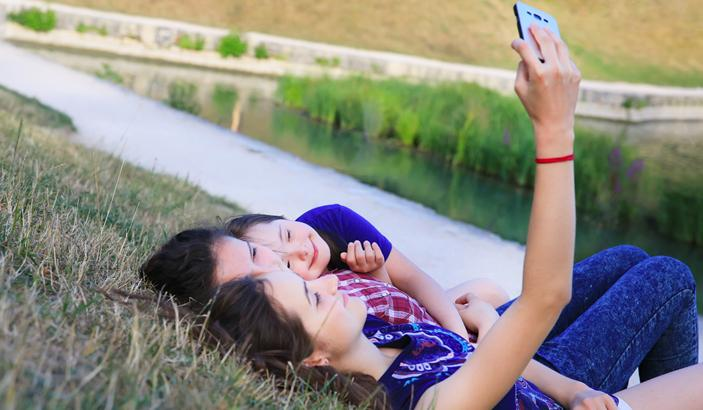 Three teenage girl_ now with an intellectual disability_ taking a selfie while lying on grass.