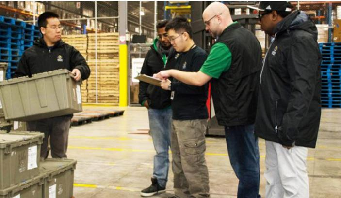Five men working in a warehouse. Some have an intellectual disability.