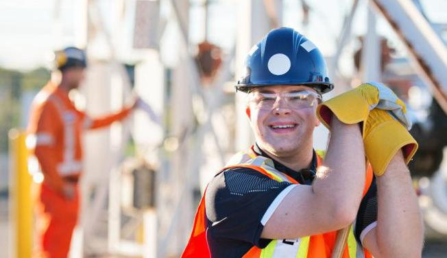 Young man with intellectual disability smiling and working in construction.