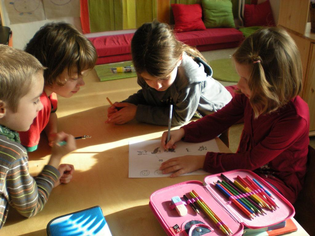 4 children sitting on the floor of a classroom drawing.