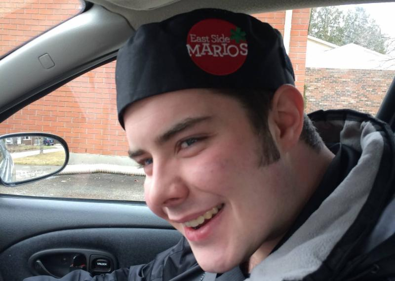 Young man named Jordan smiling at camera wearing East Side Mario_s hat.
