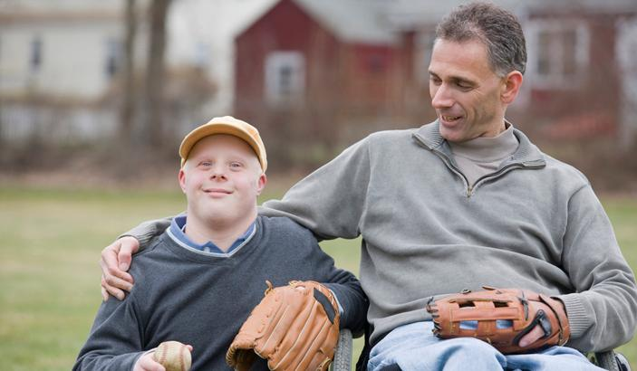 Boy with intellectual disability outside with many in wheelchair. Both are smiling and ready to play baseball.