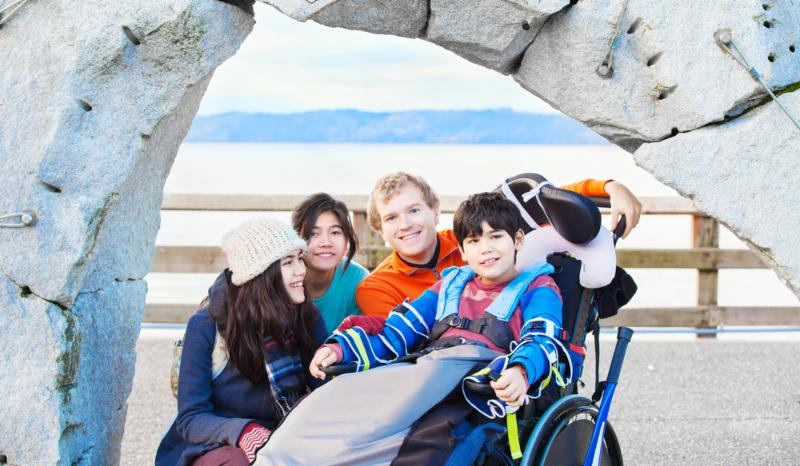 Little boy in wheelchair surrounded by family outside_