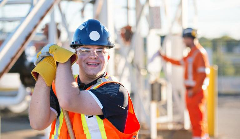 Man with an intellectual disability smiling at camera wearing construction uniform and helmet working on construction site.