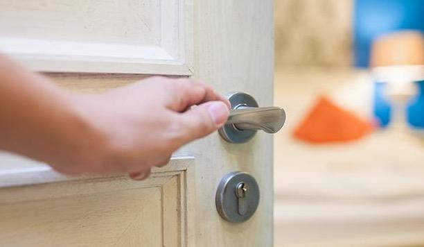Close-up of person_s hand opening door to home.