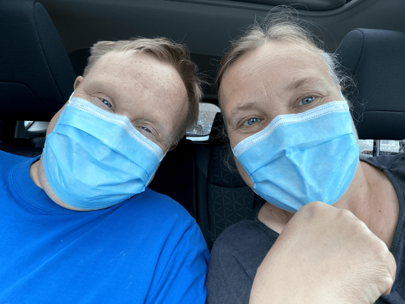 A brother in sister sitting together in a car, smiling with their masks on