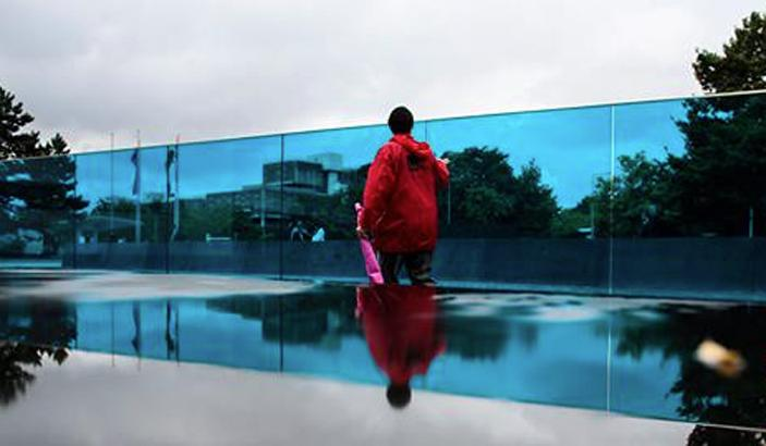 Woman walks past a memorial on a cloudy day.