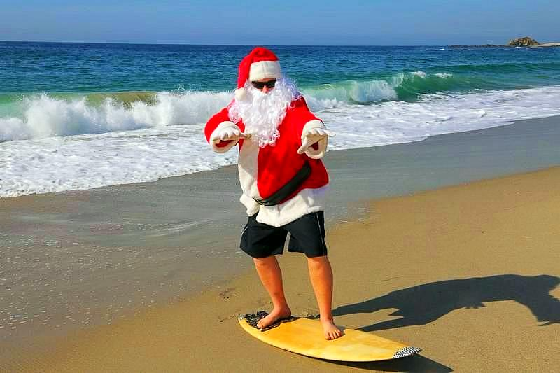 Surfing Santa. Santa Claus Surfs on his Surf Board while on a Beautiful Beach with a Blue Ocean. Focus on Santas Face Santa Vacation. Surfing Santa. Santa goes Surfing. Santa Claus enjoys the beach