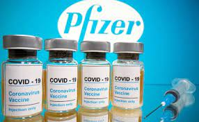 4 COVID 19 vaccine bottles and pfizer logo in background