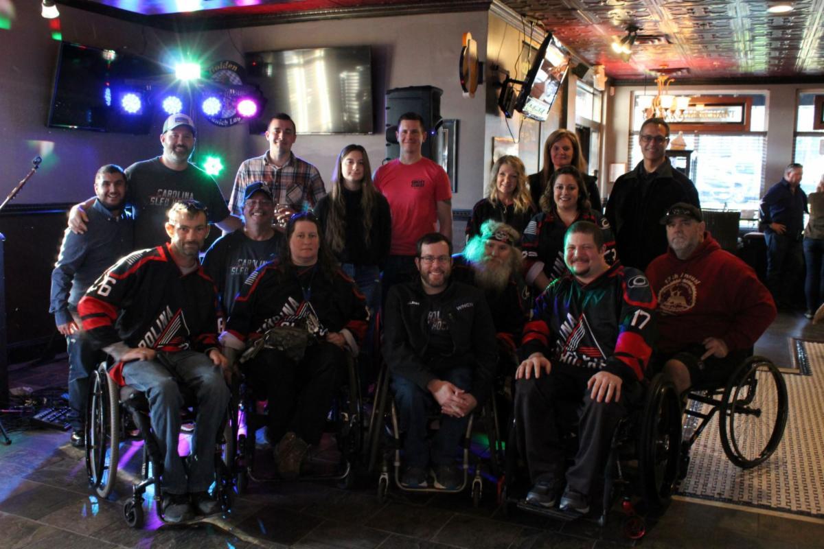 group photo of ADANC staff, board members, and Carolina Sled Hockey team