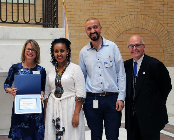 Leyla standing with her career coach and DTA officials, receiving her certificate at the State House.