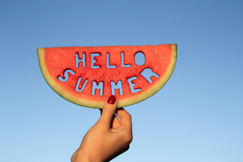 Watermelon slice  with text Hello Summer_  woman hands holding it against blue sky. Summertime concept.