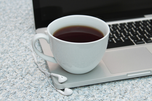 Laptop and keyboard with ear buds and tea or coffee