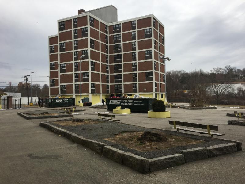 Large brick building with empty parking lot, surrounded by dumpsters. Building appears to be in disrepair. Image is of one of the condemned buildings in New London.
