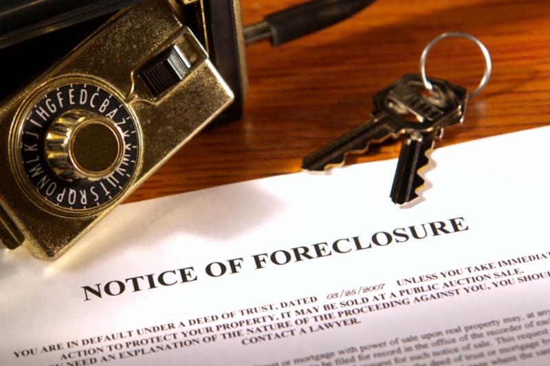 Paper that says Notice of Foreclosure, with keys on a table.