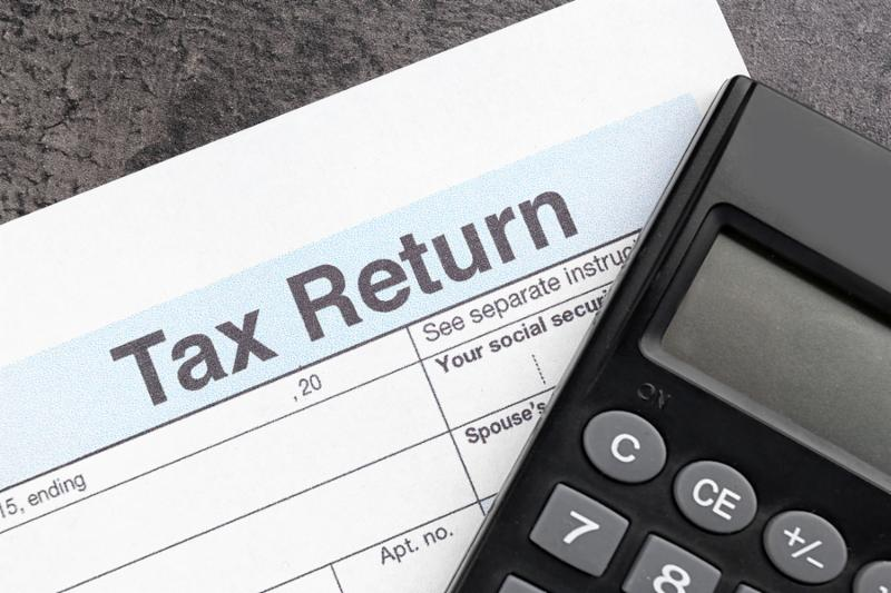 Tax return form and calculator on table