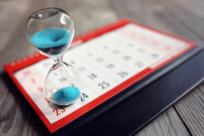 Hour glass on calendar concept for time slipping away for important appointment date_ schedule and deadline