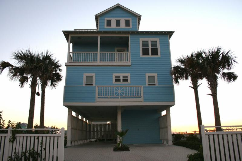 A beautiful coastal vacation home on the beach at sunset.