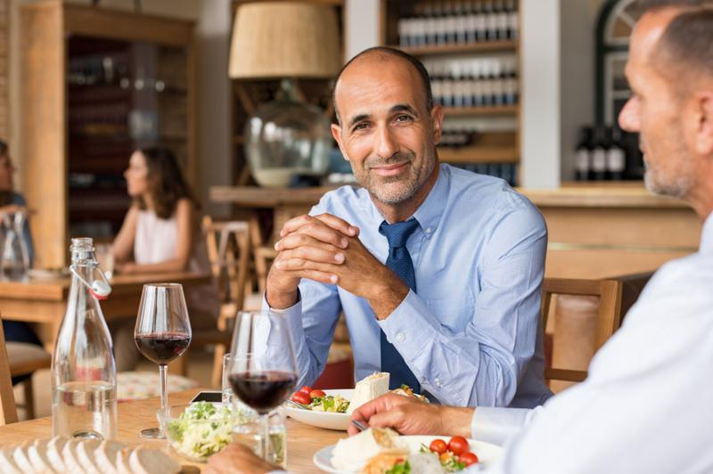 Smiling mature businessman sitting at cafe with partner enjoying meal. Portrait of senior businessman in restaurant looking at camera. Multiethnic man having an informal meeting at restaurant.