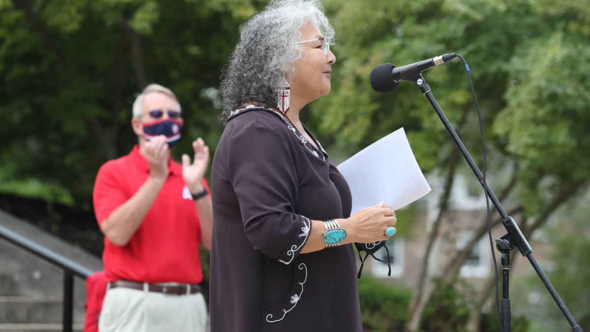 Elder Lorraine Whitman address students from the podium. President Peter Ricketts looks on and applauds.