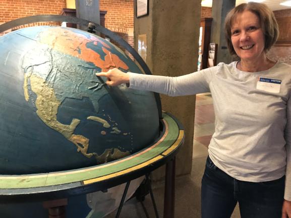 Seedlings' Karen Smith points to Livonia, MI, on Perkins giant tactile globe.