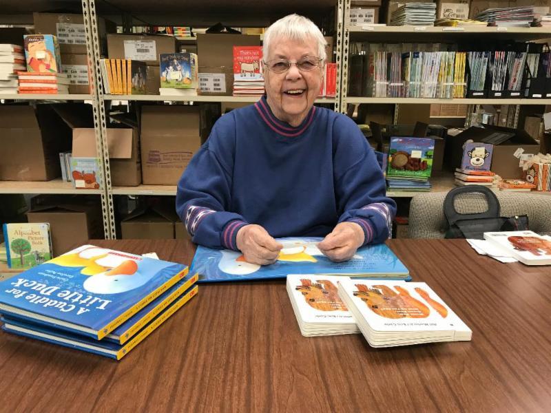 Seedlings volunteer Shirley Brown adds braille to baby board books.