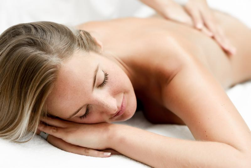 Young blond woman having massage in the spa salon. Massage and body care. Body massage treatment.