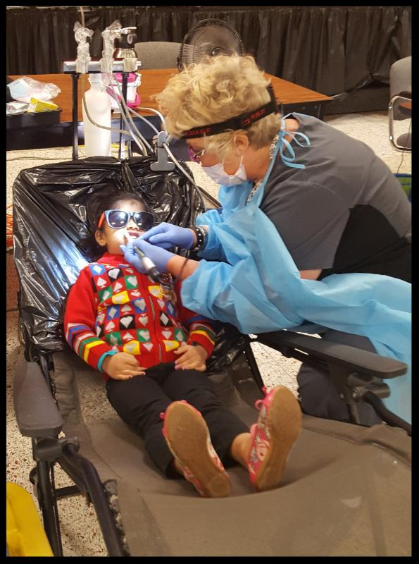 A young child is reclined back in a chair wearing sunglasses while a hygentist with a mask on her face and gloves on her hands checks his teeth.