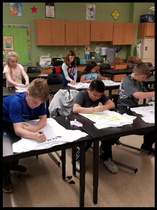 Six students are bent over t-shirts_ which they are painting with fabric paint.