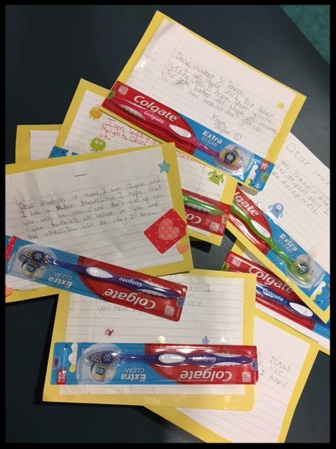 Image shows handwritten letters and packages of toothbrushes on a table.