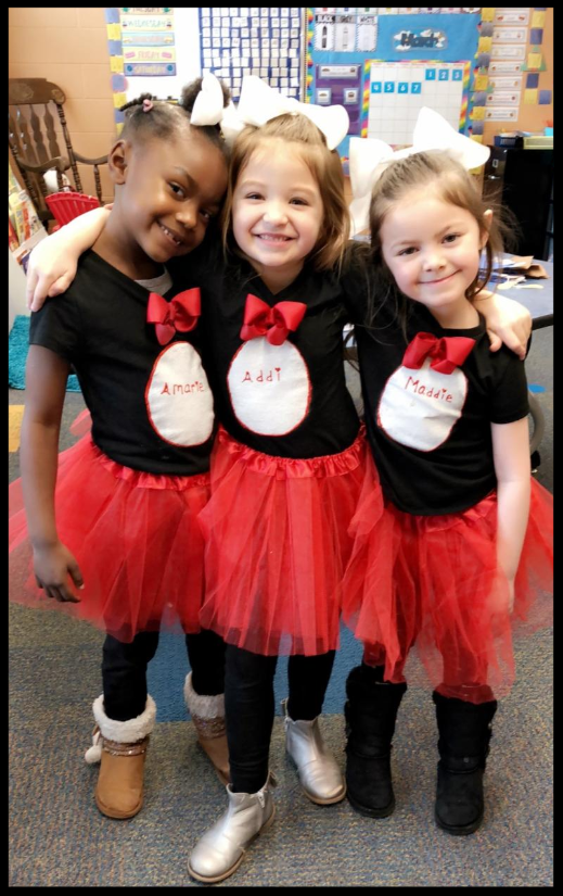 Three girls in kindergarten stand together_ their arms over each others_ shoulders. They are wearing matching outfits_ gauzy red skirts and black short-sleeve shirts that have a red bowtie and a white oval in the middle with their names written inside.