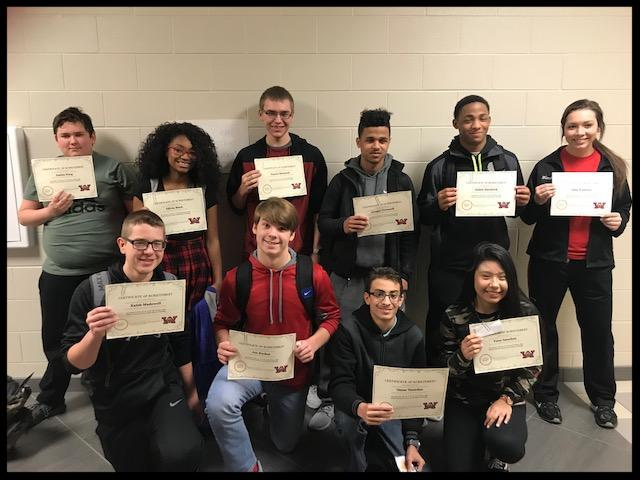 A group of 10 students stand in two rows. They are holding certificates and smiling at the camera