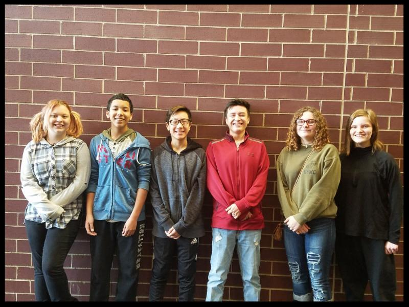 Six students stand against a brick wall_ smiling at the camera