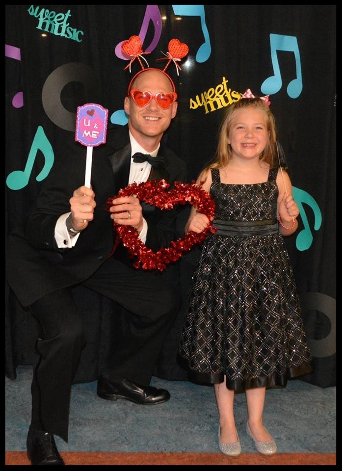A man and a little girl are in front of a backdrop that has music notes and the words _Sweet music._ The man is kneeling next to the girl. He is holding a small sign that says _U and me_. He is wearing heart-shaped glasses and has a headband with hearts on it on his head. He and the little girl are holding a heart-shaped garland.