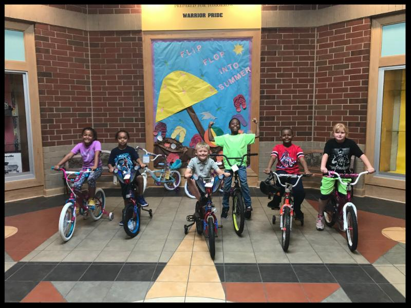 Six students are on bikes in the atrium of the school