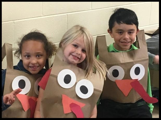 Three young students smile at the camera. They are wearing paper bag smocks that are decorated with eyes and beaks to look like turkeys