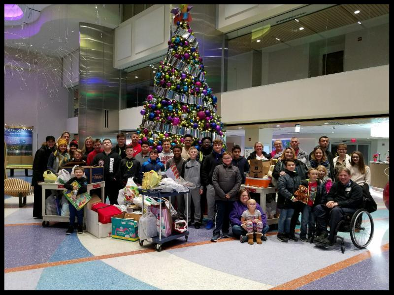 A large group of people stand around a colorfully decorated Christmas tree in an atrium_ there are wrapped presents around them.