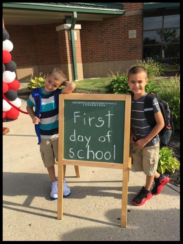 Two boys standing next to a sign that says First day of school