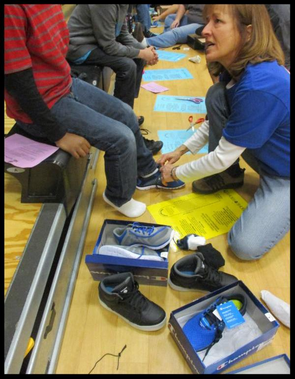 A lady puts a shoe on a boy who is sitting on a bleacher